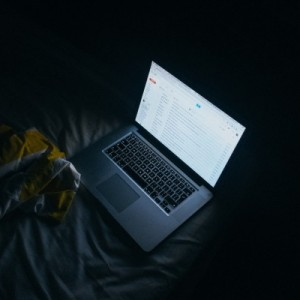 laptop-on-bed-in-dark-room