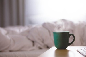 coffee-cup-on-table-with-bed-in-background