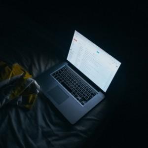 laptop-on-bed-in-dark-room
